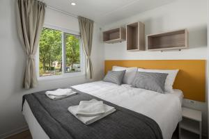 A bed or beds in a room at Camping Ulika Mobile Homes - Naturist