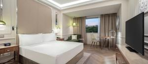 A bed or beds in a room at Athenee Palace Hilton Bucharest