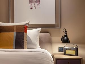 A bed or beds in a room at The Londoner