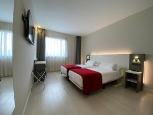 A bed or beds in a room at Hotel New Bilbao Airport