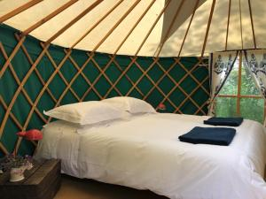A bed or beds in a room at The Glade 3 yurt Glamping Cluster