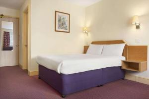 A bed or beds in a room at Days Inn by Wyndham Sevenoaks Clacket Lane