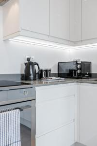 A kitchen or kitchenette at Deluxe 2 Bedroom St Albans Apartment - Free WiFi & Parking
