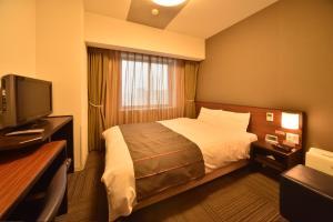 Tempat tidur dalam kamar di Dormy Inn Asahikawa