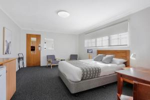 A bed or beds in a room at Tudor Motor Inn Warrnambool