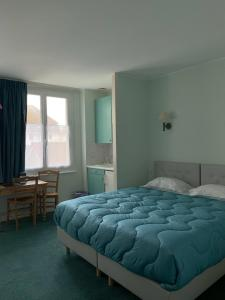 A bed or beds in a room at Hôtel Le Caddy