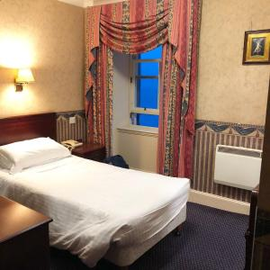 A bed or beds in a room at Queens Hotel