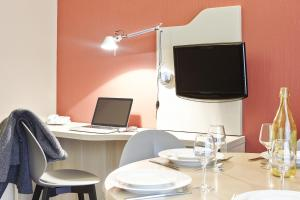 A television and/or entertainment centre at Aparthotel Adagio Marseille Prado Plage