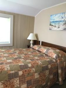 A bed or beds in a room at Kennebunk Gallery Motel and Cottages