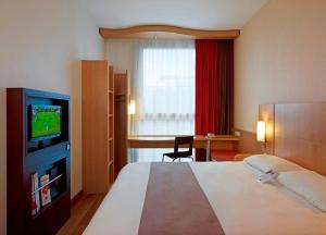 A bed or beds in a room at Ibis Warszawa Reduta