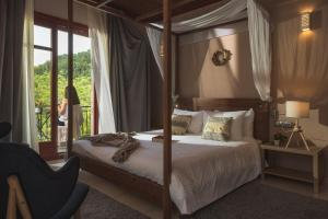 A bed or beds in a room at Rouista Tzoumerka Resort