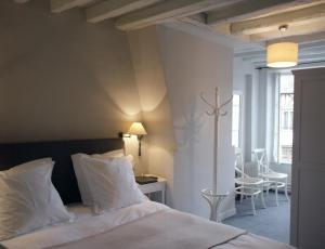 A bed or beds in a room at Hôtel La Licorne & Spa
