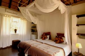 A bed or beds in a room at Normann Safari Bush Lodge