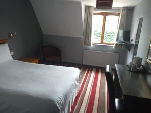 A bed or beds in a room at The Airman Hotel