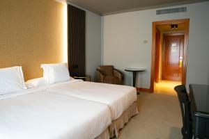 A bed or beds in a room at Hotel Sercotel Ciudad de Oviedo