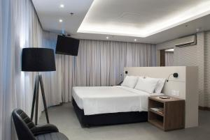 A bed or beds in a room at Master Porto Alegre Hotel