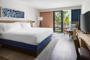 A bed or beds in a room at Hilton Garden Inn St. Pete Beach, FL