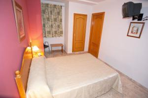 A bed or beds in a room at Hostal Miguel y Juani