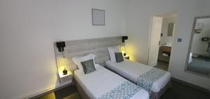 A bed or beds in a room at Hôtel L'Alsace-Gare sncf