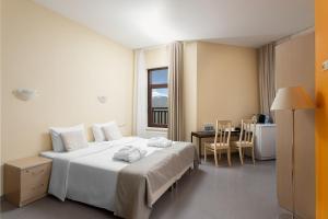 Кровать или кровати в номере Riders Lodge Роза Хутор