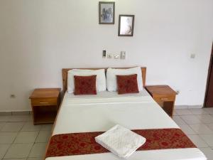 A bed or beds in a room at Imans Hotel Dabou