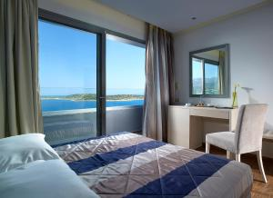 A bed or beds in a room at Mistral Bay Hotel