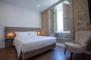 Uma cama ou camas num quarto em Solar Valadim - serviced apartments