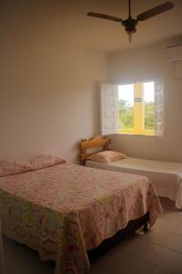 A bed or beds in a room at Pousada Pau Brasil