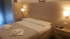 A bed or beds in a room at Hotel La Baia