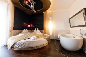 A bed or beds in a room at Maiers Kuschelhotel Loipersdorf Deluxe - ADULTS ONLY