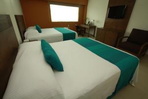 A bed or beds in a room at Hotel La Venta Inn Villahermosa