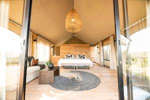 A bed or beds in a room at Mavela Game Lodge