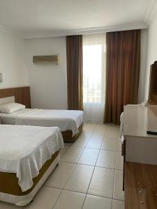 Een bed of bedden in een kamer bij Miray Hotel Kleopatra