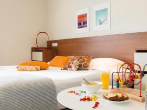 A bed or beds in a room at Hôtel Lyon Métropole
