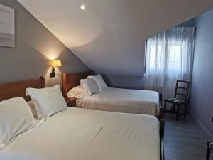 A bed or beds in a room at Hotel Arco Navia