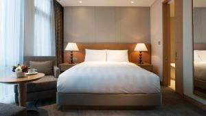 A bed or beds in a room at LOTTE City Hotel Jeju