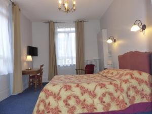 A bed or beds in a room at Hôtel des Thermes