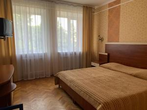 A bed or beds in a room at Hotel Prydesnyansky