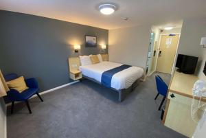 A bed or beds in a room at Days Inn Hotel Sedgemoor