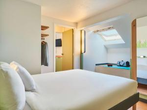 A bed or beds in a room at Ibis Budget Versailles Coignieres