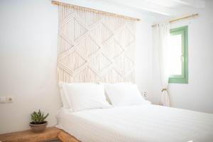 A bed or beds in a room at Levantes Ios Boutique Hotel