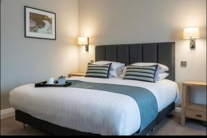 A bed or beds in a room at Aberystwyth Park Lodge Hotel