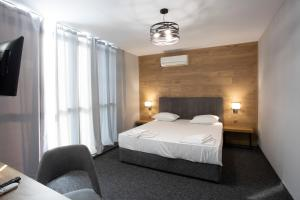 A bed or beds in a room at Avenue Hotel Deluxe