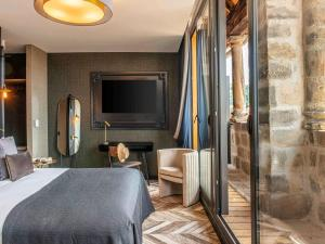 A bed or beds in a room at Mercure Figeac Viguier du Roy