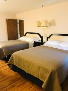 A bed or beds in a room at Sunset Inn