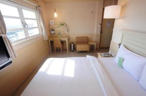 A bed or beds in a room at Kindness Hotel - Tainan Minsheng