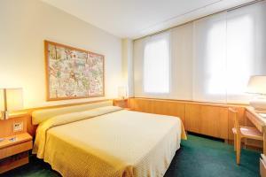 سرير أو أسرّة في غرفة في فندق غاليليو