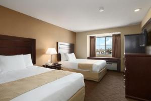 A bed or beds in a room at Microtel by Wyndham Cedar Rapids/Marion