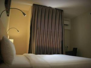 A bed or beds in a room at Biz Hotel Batam