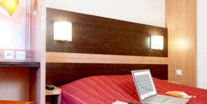 A bed or beds in a room at Premiere Classe Avignon Le Pontet